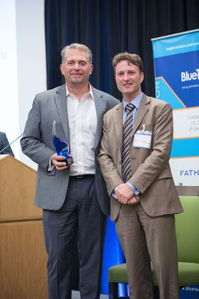 Paul O'Callaghan, chief executive of BlueTech Research, presents Trevor Hill, chairman and chief Executive of Fathom, with the Blue Truffle Award at BlueTech Forum.