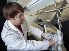 Georgia Tech researcher Andrew Brown places a finished hollow fibre metal-organic framework (MOF) membrane module into a membrane testing apparatus to measure its gas separation properties. (Credit: Rob Felt)